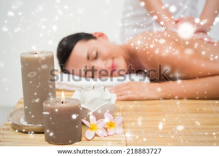 Beautiful brunette enjoying a back massage against snow falling - stock photo