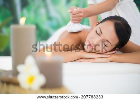 Beautiful brunette enjoying a herbal compress massage at a luxury spa - stock photo