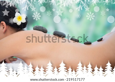 Beautiful brunette enjoying a hot stone massage against fir tree forest and snowflakes - stock photo
