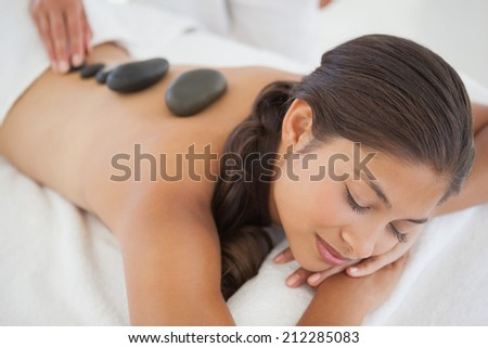 Beautiful brunette enjoying a hot stone massage at the health spa - stock photo