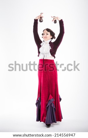 beautiful brunette female spanish flamenco dancer in white blouse and vinous flamenco skirt dancing with castanets in her arms in studio on gray background - stock photo