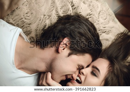 beautiful brunette girl biting the guy's nose. The concept of tenderness and affection in bed - stock photo
