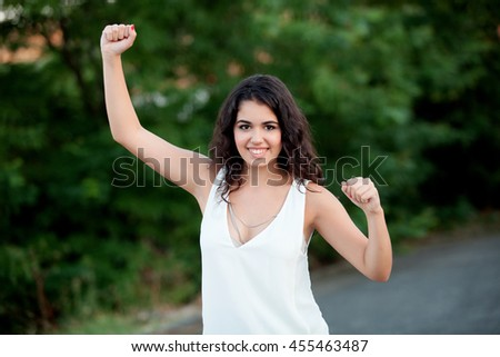 Beautiful brunette girl celebrating something in the park with many plants of background - stock photo