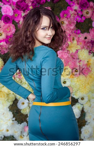 Beautiful brunette girl in blue dress smiling in the studio with flowers background  - stock photo