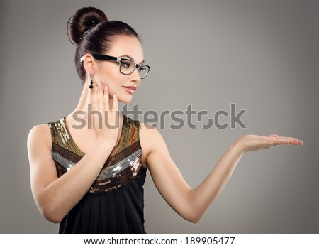 Beautiful brunette girl in eyewear showing something. Young attractive Caucasian woman model in stylish dress wearing optical eyeglasses.  - stock photo