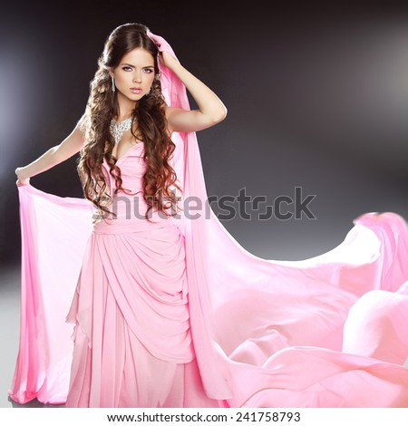 Beautiful brunette girl model in blowing transparent chiffon dress. Long wavy hair styling.  - stock photo