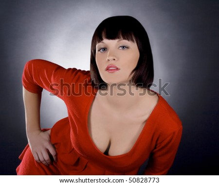 Beautiful brunette girl posing in studio on dark background - stock photo