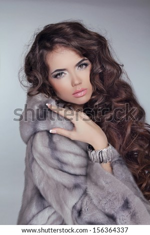 Beautiful brunette girl wearing in mink fur coat with long hair styling isolated on grey background. Fashion winter woman model posing. - stock photo