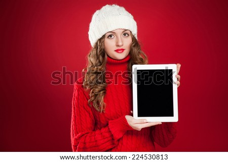 beautiful brunette girl wearing red sweater and holding ipad over red background  - stock photo