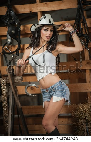 Beautiful brunette girl with country look, indoors shot in stable, rustic style. Attractive woman with cowboy hat, denim shorts and tight white top. American country style farmer near barn harness - stock photo