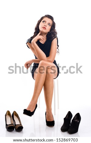 beautiful brunette girl with long hair chooses shoes  isolated on white background - stock photo