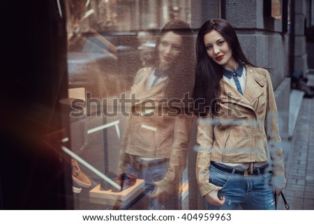 Beautiful brunette girl with perfect make-up, red lips, wearing a beige coat, white shirt, posing  in just bought things near glass wall of the shopping center. Beautiful reflections from glass - stock photo