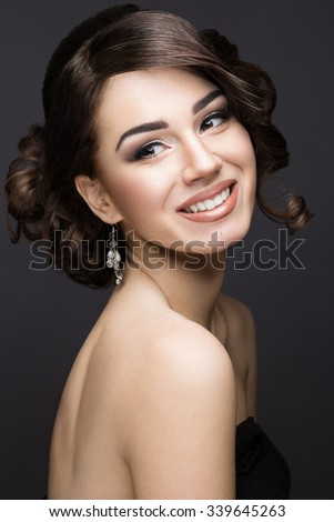 Beautiful brunette girl with perfect skin, evening make-up, wedding hairstyle and accessories. Beauty face. - stock photo