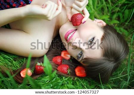 Beautiful brunette girl with strawberry - stock photo