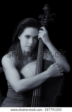 Beautiful brunette holding a cello with selective light in red dress artistic conversion - stock photo