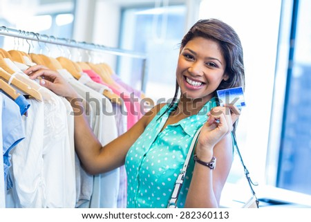 Beautiful brunette holding credit card in clothes store - stock photo