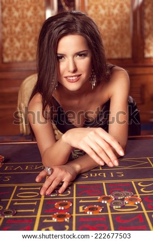 Beautiful brunette in a black dress playing in the casino. - stock photo