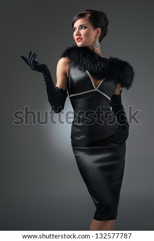beautiful brunette in a black dress with fur collar - stock photo