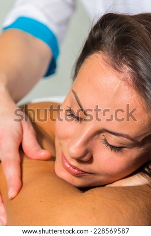 Beautiful brunette in a spa salon. Girl lying on the couch and make her a massage room. Spa massage, relaxing massage, masseuse, relaxation, rest - body care concept. - stock photo