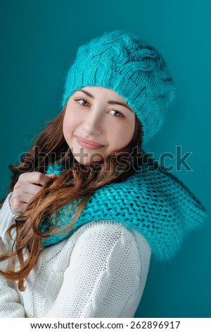 Beautiful brunette in a turquoise knitted hat and scarf smiling. - stock photo