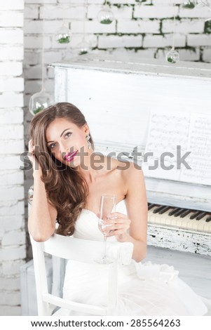 beautiful brunette in a wedding dress with a glass of champagne - stock photo