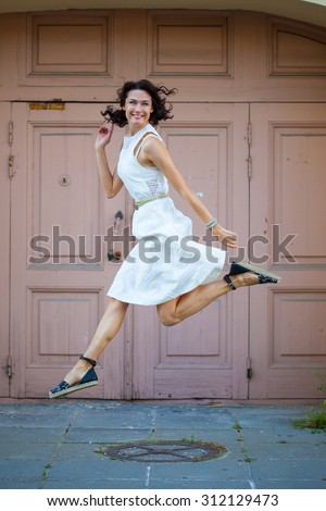 beautiful brunette in a white dress jumped on the background of old doors - stock photo