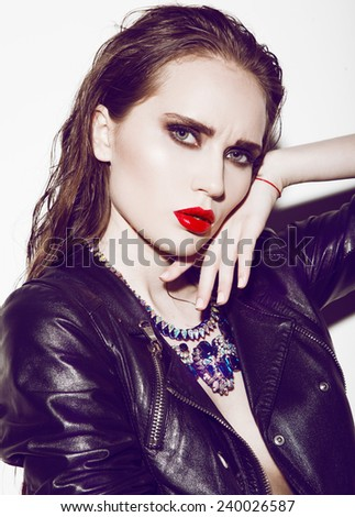Beautiful brunette in aviator's leather jacket with red lips - stock photo