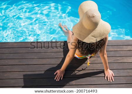 Beautiful brunette in bikini sitting by the pool paddling on a sunny day - stock photo