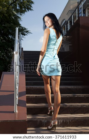 beautiful brunette in blue dress goes on steps - stock photo