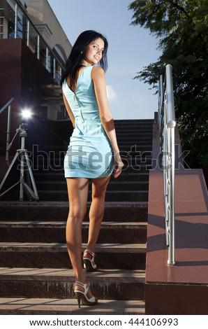 beautiful brunette in blue dress goes on steps - stock photo