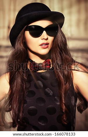 Beautiful brunette in bowler hat and bow-tie standing on the street of the old town. Retro style. - stock photo