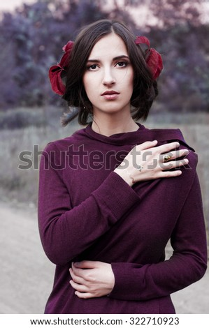 Beautiful brunette in purple sweater and red leaves in her hair outdoor autumn portrait - stock photo