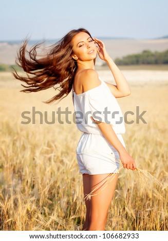 beautiful brunette in the  field - stock photo