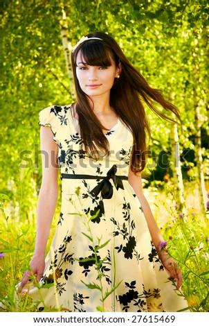 Beautiful brunette in white dress against birchwood. - stock photo