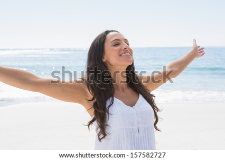 Beautiful brunette in white sun dress enjoying the sun on the beach - stock photo