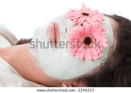 Beautiful brunette lying for a spa treatment with flowers on her eyes - stock photo