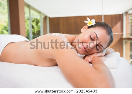 Beautiful brunette lying on massage table with salt scrub on back in the health spa - stock photo
