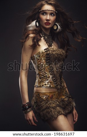 Beautiful brunette model dressed as Indian posing in studio - stock photo