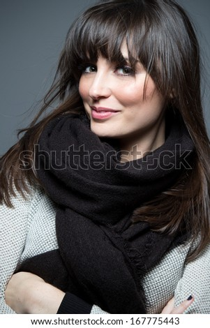Beautiful brunette model wearing scarf and sweater, poses for camera. - stock photo