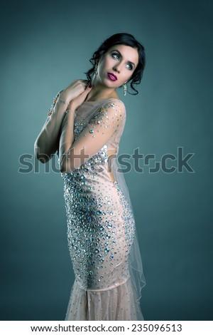 Beautiful brunette posing in elegant evening dress - stock photo
