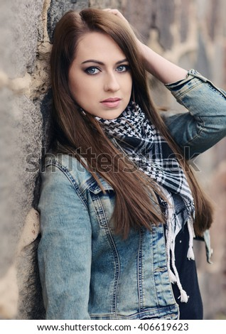 Beautiful brunette posing over stone wall - stock photo