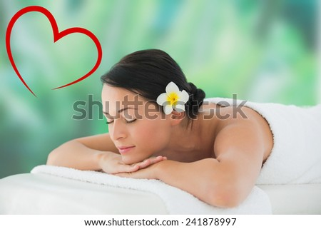 Beautiful brunette relaxing on massage table against heart - stock photo