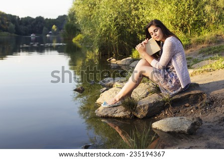 Beautiful brunette senior woman studying for her exams sitting on a rocks near river reading book in a dress. Warm Sunset. Outdoors. Copy Space - stock photo