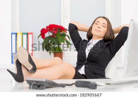 beautiful brunette sitting in chair and relaxing. attractive girl daydreaming at desk and resting - stock photo