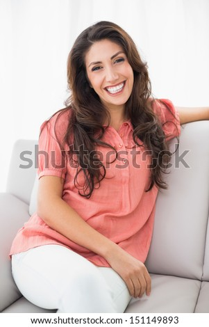 Beautiful brunette sitting on her couch smiling at camera at home in the living room - stock photo