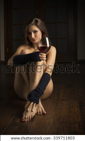 beautiful brunette sitting on the floor , naked with gloves . with a galss of red wine near her . she looks very sensual - stock photo
