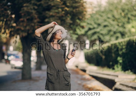beautiful brunette smoke electronic cigarette in public places - stock photo
