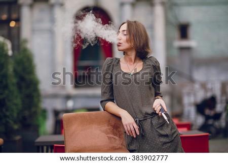 beautiful brunette smoke electronic cigarette on the summer terrace of restaurant - stock photo