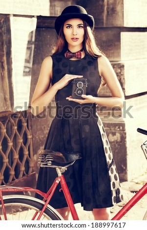 Beautiful brunette standing near her old bicycle and holding the old camera over city background. Retro style. - stock photo