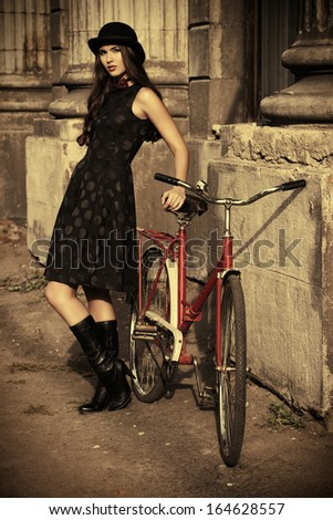 Beautiful brunette standing near her old bicycle over city background. Retro style. - stock photo